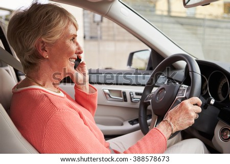 In car view of senior female driver speaking on her phone