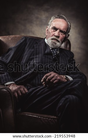In chair sitting characteristic senior business man. Smoking cigar. Gray hair and beard wearing blue striped suit and tie. Against brown wall. - stock photo