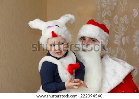 in Christmas night the boy in a suit of a rabbit meets Santa Claus