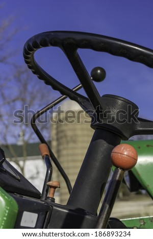 In control on the farm: Closeup of steering wheel and shift gears of tractor near silo and outbuilding on a public farm in northern Illinois, USA, on a sunny day in spring
