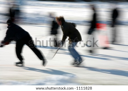 in denmark the winter with people ice skating and playing hockey, low shutter speed and panning