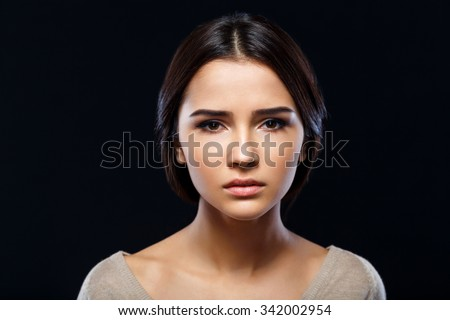 In desperate need. Close up of poor sad depressed young woman  begging for help and going to cry while standing isolate on black background - stock photo