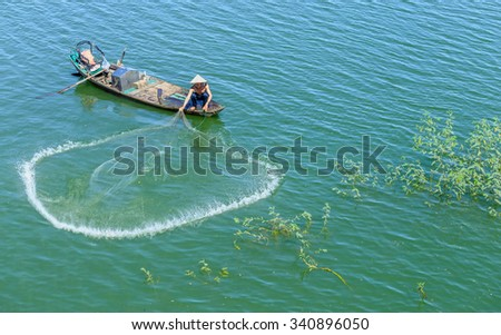 In Dong Nai, Vietnam - November 15th, 2015: The fishermen casting their nets to catch fish circle improves a better life in the winter morning at Tri An, Dong Nai, Vietnam.