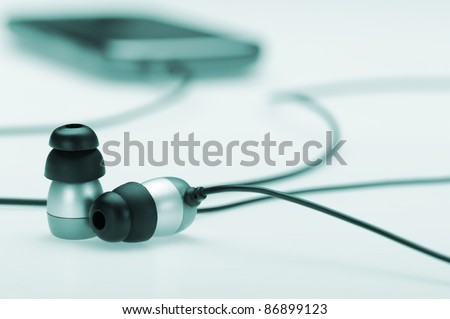 in ear headphone with mobile audio player on bokeh background. Blue toned - stock photo