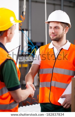 In factory male engineer and workman shake hands