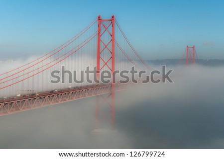 In fog days part of the 25th bridge on Lisbon disappears - stock photo