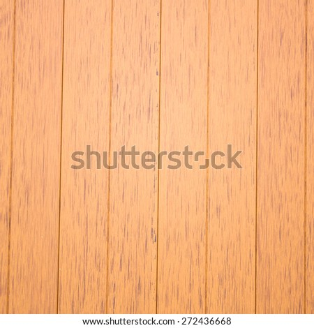 In front of a panel of Faux wood.