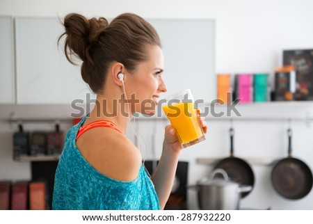 In her modern kitchen, a woman in profile is about to drink her freshly-made smoothie, which is packed with vitamins. A healthy lifestyle is so much fun. - stock photo