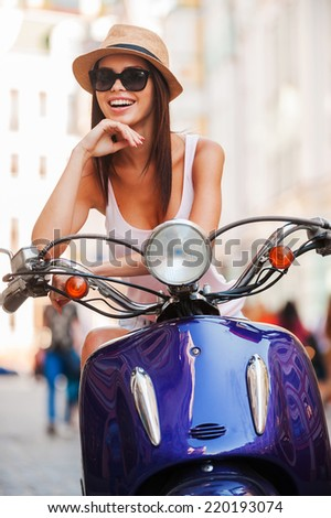 In her own style. Beautiful young woman in funky hat sitting on scooter and smiling - stock photo
