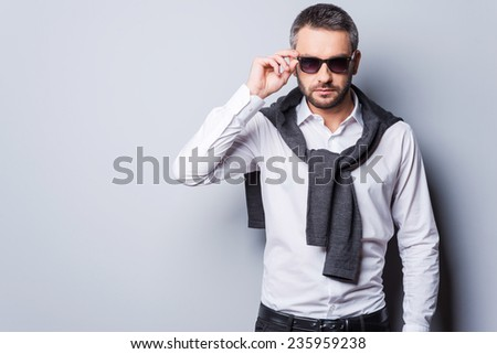 In his own perfect style. Handsome young man in smart casual wear adjusting his sunglasses and looking at camera while standing against grey background - stock photo