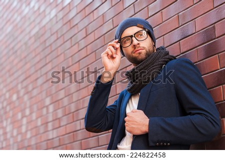 In his own perfect style. Low angle view of handsome young man in smart casual wear adjusting his eyeglasses and looking away while standing against brick wall - stock photo