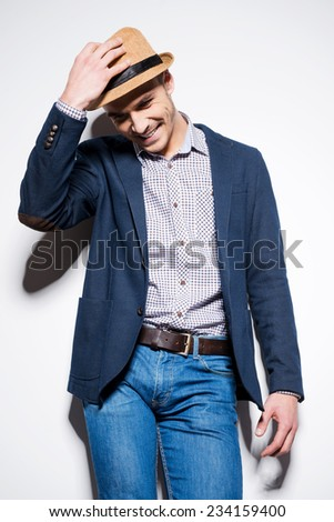 In his own style. Handsome young man in smart casual wear adjusting his fedora and smiling while standing against a wall - stock photo