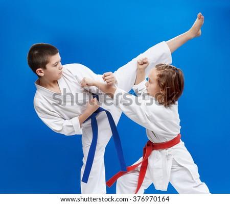 In karategi small athletes train kick leg and punch arm - stock photo