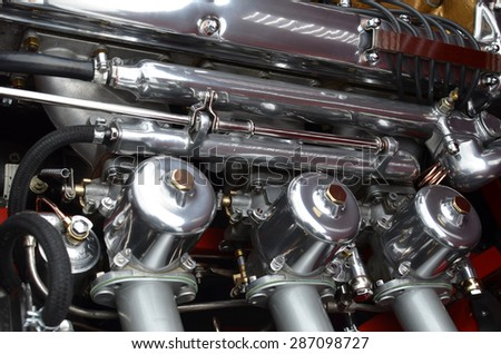 In-line carburetors on a classic sports car.