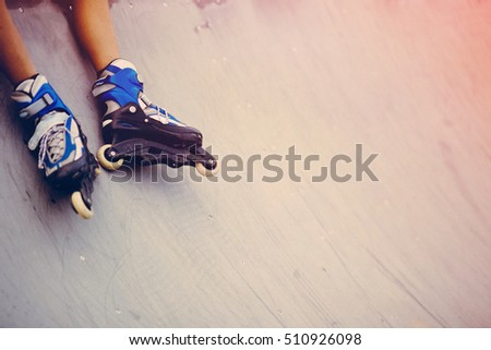 in line skates on skate ramp. young boys legs in skate park. copy space