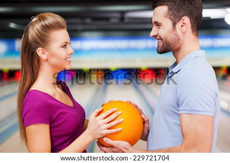 In love against the background of bowling alleys. Cheerful young couple looking at each other and holding bowling balls while standing against bowling alleys  - stock photo