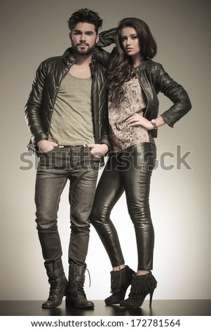 in love couple dressed in leather clothes in a fashion pose in studio - stock photo