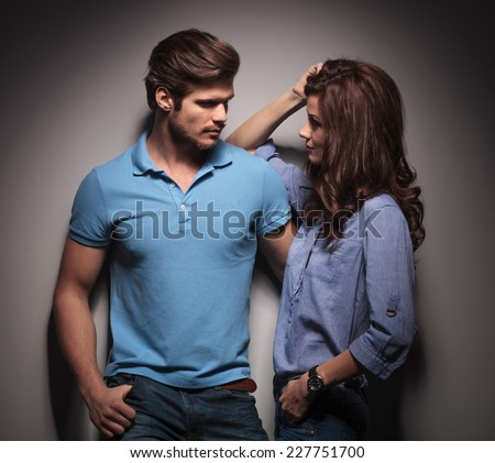 In love couple looking at each other, the woman is leaning on her lover while he is holding her with his left hand. - stock photo