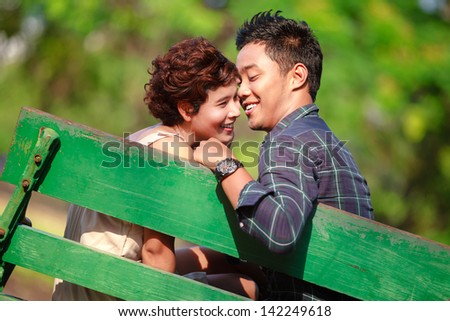 In love couple sitting on bench in the park - stock photo