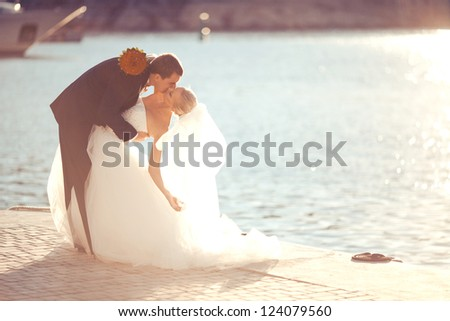in love with a beautiful young bridal couple kissing at the sea in a sunny day - stock photo