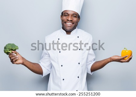 In love with healthy food. Cheerful young African chef in white uniform holding pepper in one hand and broccoli in another while standing against grey background - stock photo