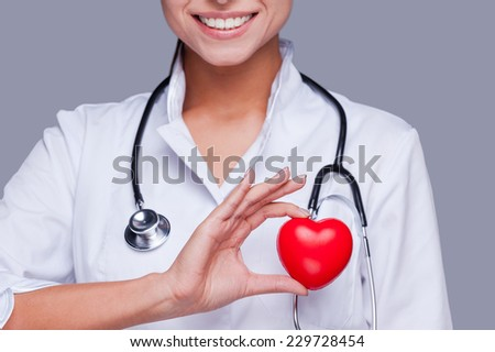 In love with her profession. Close-up of female doctor in white uniform holding heart prop and smiling  - stock photo