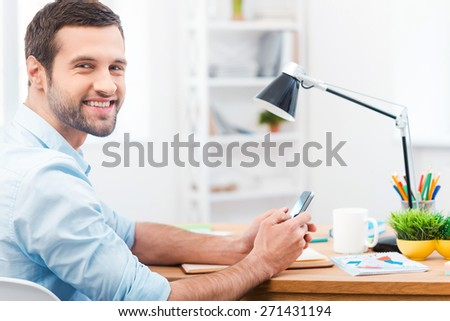 In love with my job. Side view of handsome young man in shirt holding mobile phone and smiling at camera while sitting at his working place - stock photo
