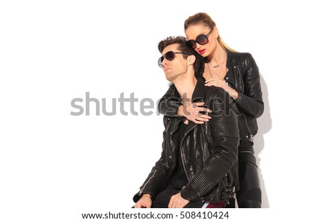 in love young couple posing in studio, man is sitting on chair and woman is holding him