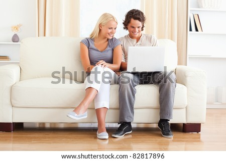 In love young couple using a laptop while sitting on a sofa - stock photo