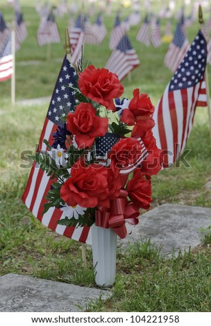 In Memory -- Flowers and flags stand in memory of the good folks who have served our country. - stock photo