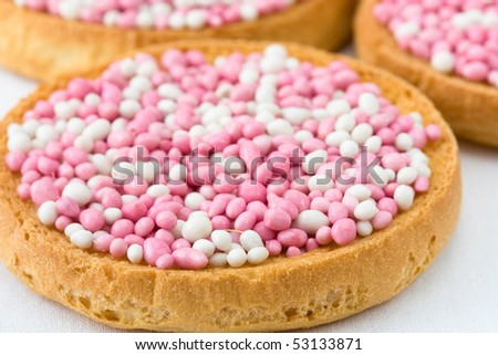 In Netherlands, it is a custom at birth of a baby girl to eat pink white muisjes on top of Dutch biscuits or round rusks. Muisjes are made of aniseed sprinkles with sugared outer layer - stock photo