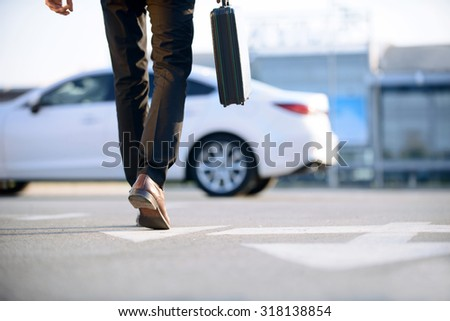 In pace of time. Modern young businessman holding case and going to his car while evincing confidence. - stock photo