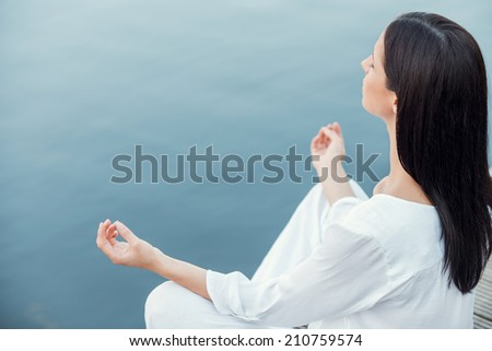 In peace with universe. Top view of beautiful young woman in white clothing meditating while sitting on the wooden quayside - stock photo