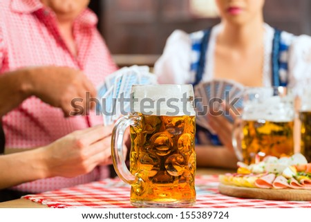 In Pub - friends in Tracht, Dirndl and Lederhosen drinking a fresh beer in Bavaria, Germany playing cards - stock photo