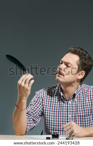 In retro style. Close-up of man looking at feather pen while sitting against grey background - stock photo