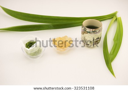 In row is finely blended pandan leaf in paper tea bag, a clear bowl of golden rock sugar for sweet taste and brewed hot tea in chinese tea cup. Blur long pandan leaves at the background on white. - stock photo
