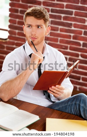 In search of inspiration. Thoughtful young man in shirt and tie writing something in note pad and looking away while sitting at his working place - stock photo