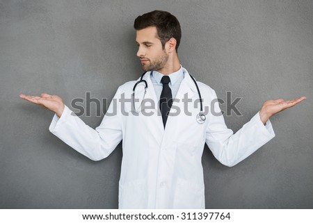 In search of right medical solution. Handsome young doctor in white uniform stretching out his arms while standing against grey background - stock photo