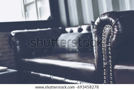 In selective focus to soft focus of Young businessman stretching leg on sofa in classy coffee shop. Interior of coffee shop with customer using digital devices on free wifi internet service.