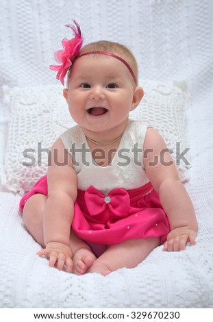 in-studio shoot of cute baby girl smiling siting on soft blanket in nice pink dress
