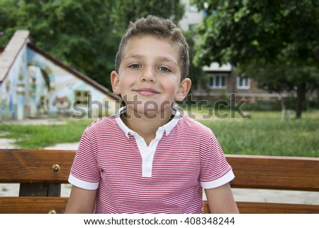 In summer, a bright sunny day in the park smiling curly-haired boy sitting on a bench.