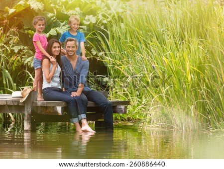 in summertime, portrait of an happy family, parents sitting at the edge of a wood pontoon, feet in the river, their two child behind them,  looking at the camera - stock photo