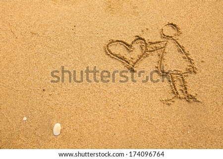 In texture of sand: girl holding a big heart. - stock photo