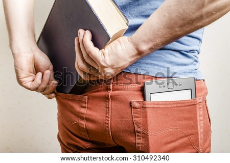 in the back pocket of jeans is an e-book, a man tries to shove in a second pocket thick old paper book - stock photo