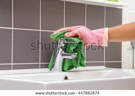 In the bathroom, ceramic sink, tiles and water tap washing and polishing. Maid or housewife cleans house. General cleaning or regular wash up.  - stock photo