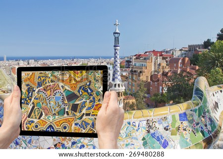 In the bottom left of the photo are hands holding tablet, whose screen contains photo of mosaic detail.  Background of the photo contains view of Barcelona. (Barcelona, Catalunya, Spain)