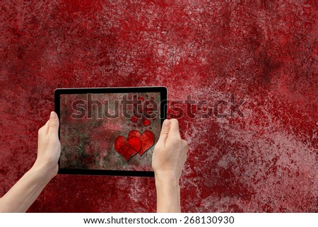 In the bottom left of the photo are hands holding tablet, whose screen contains photo of the grunge red and black texture background with the red hearts. Background is iron grunge texture background.  - stock photo
