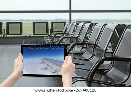 In the bottom left of the photo are hands holding tablet, whose screen contains photo of wing aircraft in flight  Background of the photo contains an empty gate at the airport.  - stock photo