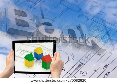 In the bottom left of the photo are hands holding tablet, whose screen contains photo of wooden tubes. Background of the photo contains abstract of the blueprint and bank inscription on the blue sky. - stock photo