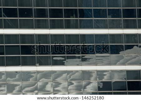 "In the business district of Paris, so called ""La Defense"", sky and the clouds make pretty reflections on the glass facade of buildings. Sometimes, desk lamps appear as light spots behind the windows. - stock photo"
